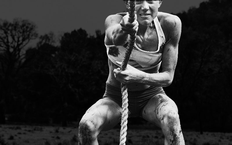 Athletic woman pulling rope