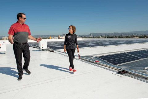 Mike Bohn and Carol L. Folt check out Galen Center solar panels