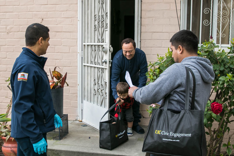 Eduardo Ibarra, right, and California State Assemblyman Miguel Santiago deliver to residents in Ramona Gardens
