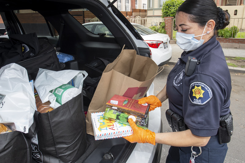 USC Department of Public Safety staff member distributes care packages of books, food and more to local families.