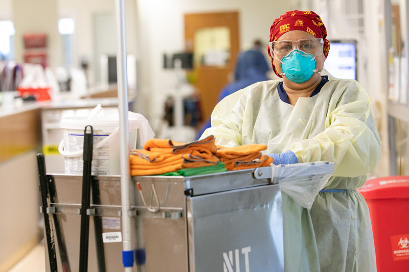 Maria Saravia with cleaning gear and disinfecting supplies at hospital