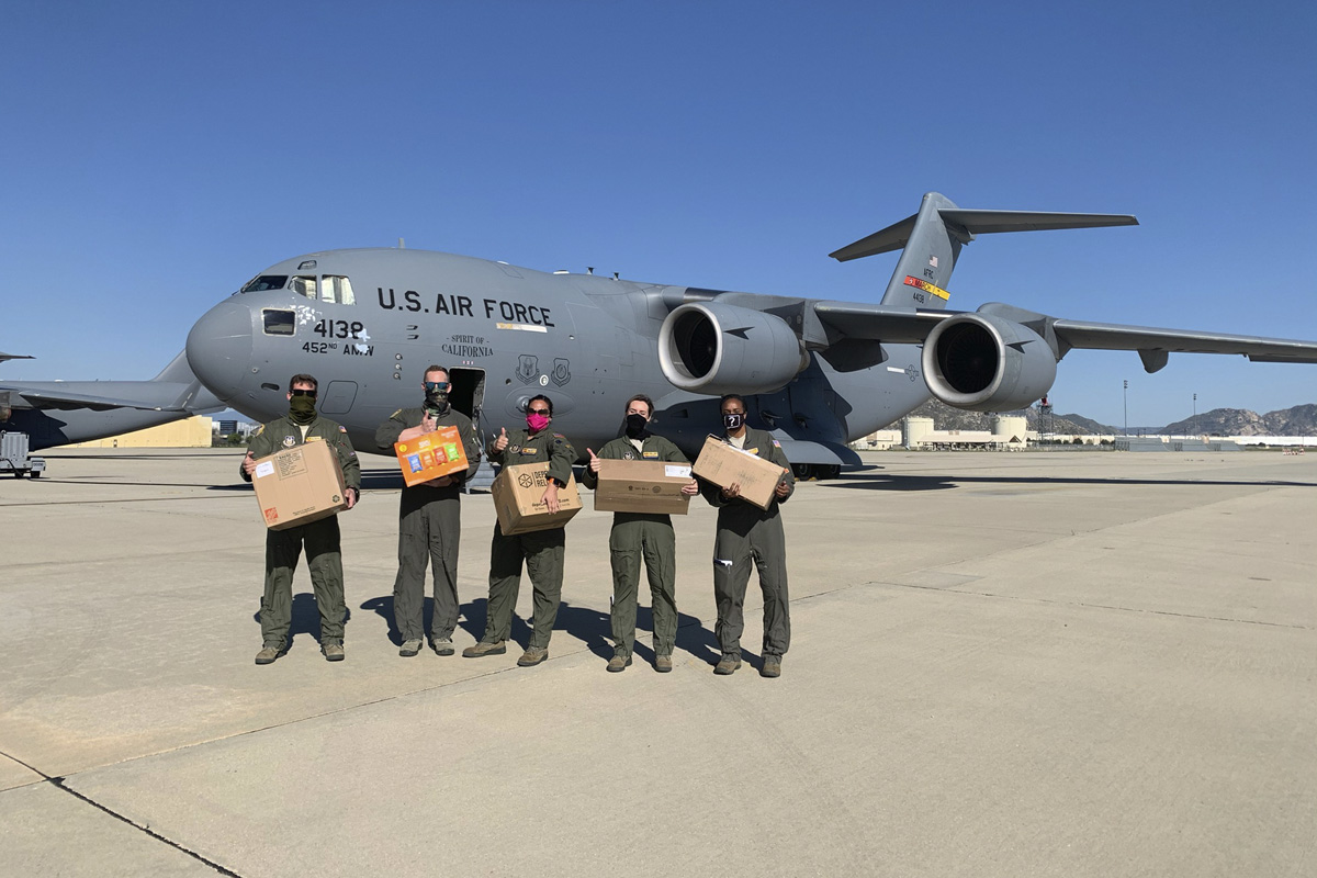 Air Force pilots standing in front of a cargo plane with boxes of face masks and supplies