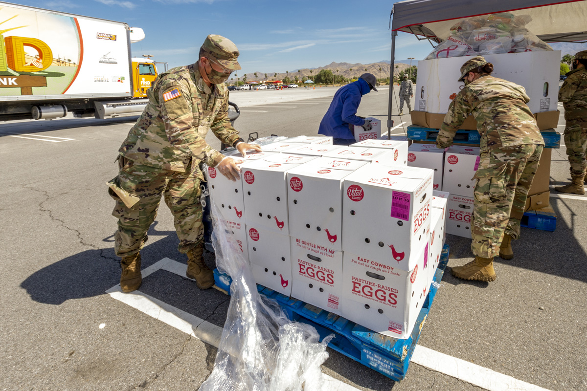 Lt. Justin Lee in fatigues and mask helping to stack boxes of eggs and food supplies.