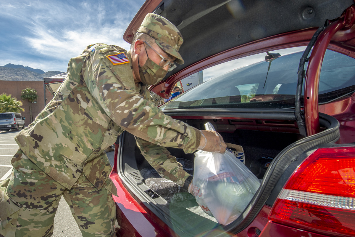 Lt. Justin Lee in fatigues and mask placing bag of food supplies in trunk of a car