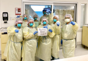"Keck nurses wearing yellow PPE gowns, holding ""Please Stay Home"" sign"