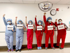 "Keck 6th Floor nurses with fists up and holding signs that read ""Stay Home Save Lives Quaran Team"""