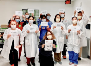 """Keck Lab"" pathology group with signs that read ""we stay here for you, please stay home for us"""