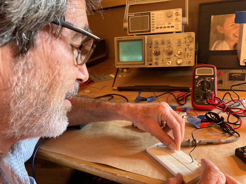 Professor Jack Feinberg uses a physics kit to build circuits for an online class in electricity and magnetism.