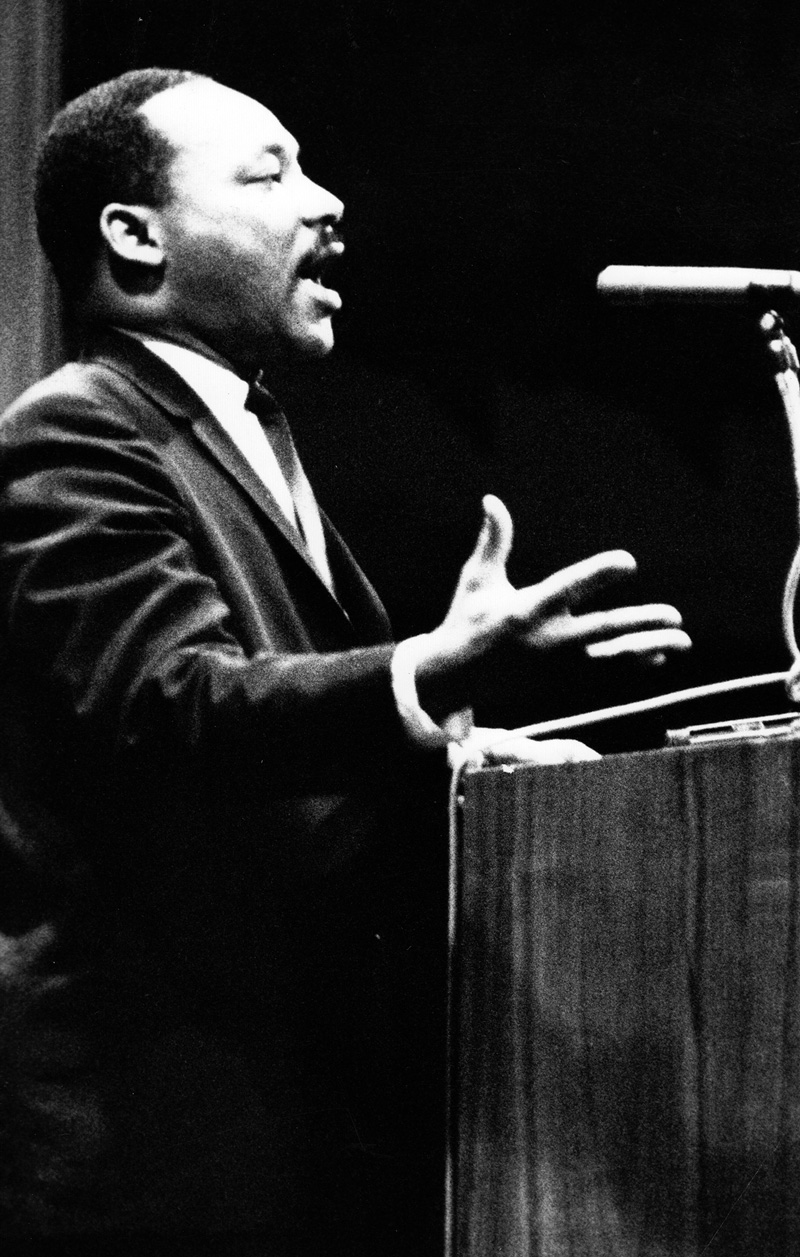 Martin Luther King Jr. stands at a podium on the stage of Bovard Auditorium.