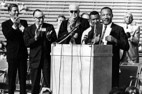 Martin Luther King Jr. at a podium flanked by other rally attendees at the Los Angeles Memorial Coliseum.