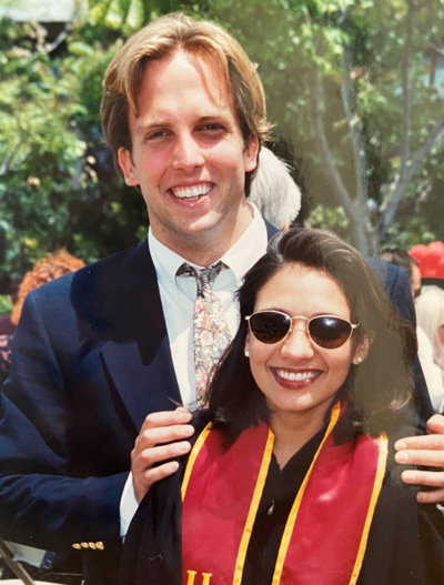 Catherine Barry in formal attire and a USC graduation sash and Tad Barry in a suit and tie.