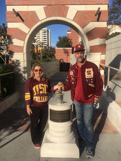 Melanie and Rob Cuddy in USC clothing at the entrance to USC's John McKay Center.