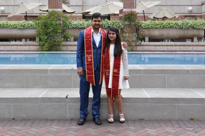 Anjali Krishna Prasad and Vipin Dwivedi in formal clothing and USC graduation sashes in front of reflecting pool at Leavey Library.