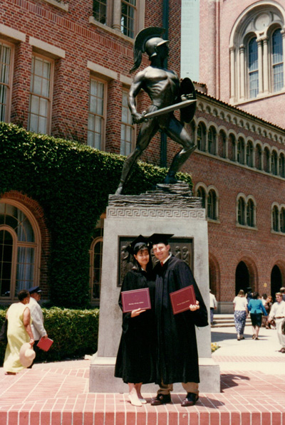Joyce and Craig Rohan in graduation robes and hats holding USC degree booklets in front of Tommy Trojan.