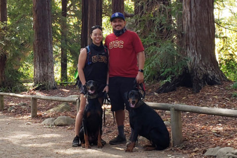 Dahliena and Bryan Chavac in USC shirts with their two Doberman Pinscher dogs on a forest trail.