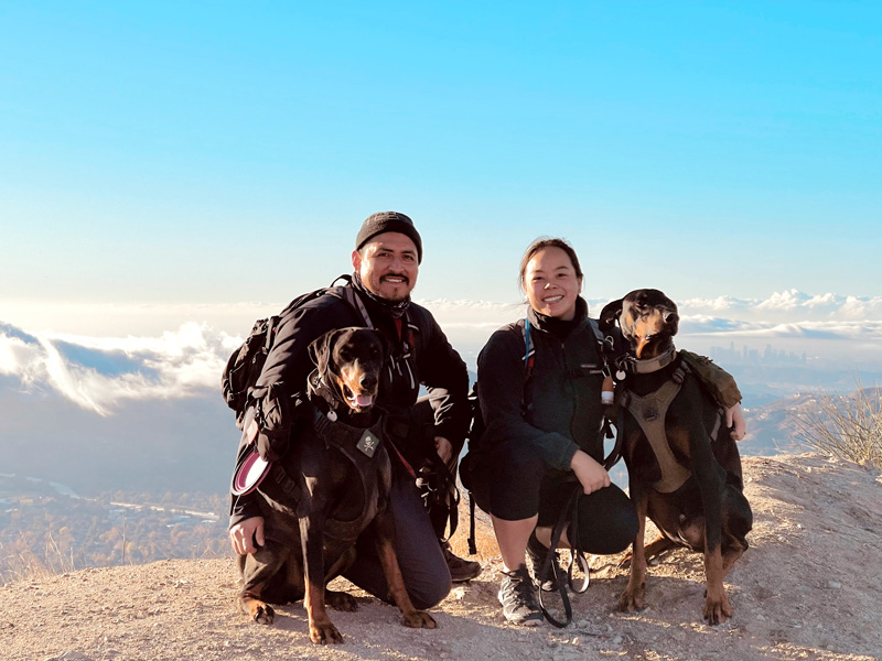Dahliena and Bryan Chavac on a mountaintop overlooking the Los Angeles skyline with their two Doberman Pinscher dogs.
