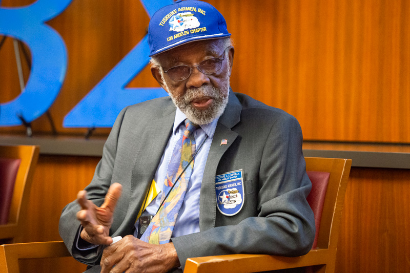 Ted Lumpkin in a suit and tie with a blue Tuskeegee Airmen Los Angeles Chapter hat and badge.