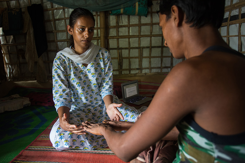 Parveen Parmar in white shirt with a blue-and-yellow pattern conducting a physical exam of a Rohingya man while seated on the floor in a refugee camp building