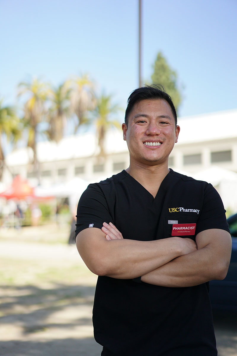 Richard Dang in a black T-Shirt with a USC Pharmacy logo and a red pharmacist badge standing in front of the Lincoln Park vaccination site.