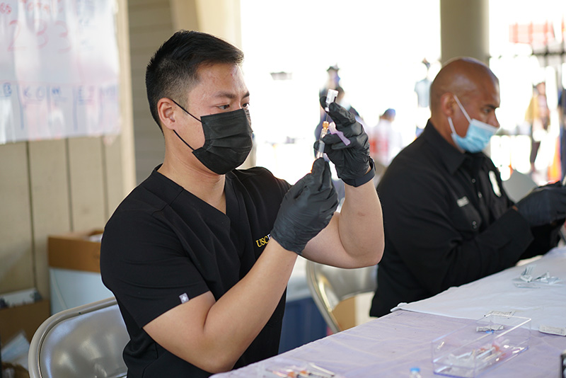 Richard Dang in a black T-shirt, black face mask, and black medical gloves holding a syringe and vial of COVID-19 vaccine.