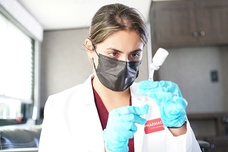 Negin Sazgar in a white lab coat, black face mask and blue medical gloves holds a syringe and vial of COVID-19 vaccine.