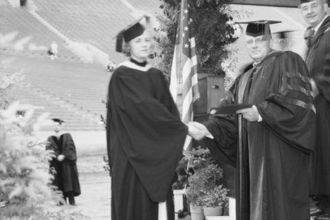 1934 USC Vice President Frank Touton hands daughter her diploma