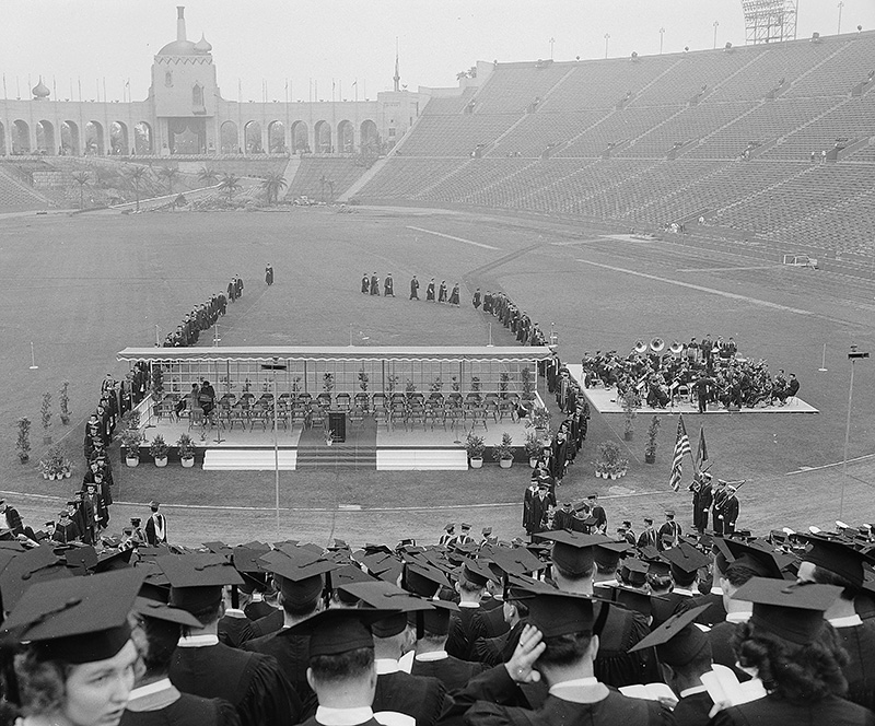 A view from the student section shows graduates seated facing a long stage with faculty and musicians seated.