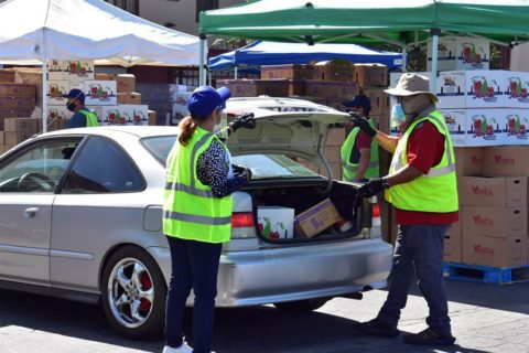 Volunteers from the USC Leslie and William McMorrow Neighborhood Academic Initiative assist with food distribution at St. Agnes Catholic Church. (Photo/Michael Morales)