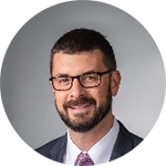Joe Landon in a gray suit and purple tie