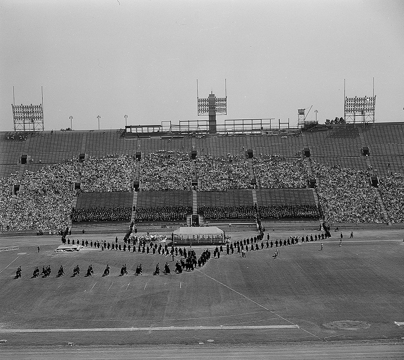 A line of graduates in caps and gowns stretches across the Coliseum field in front of seats filled with onlookers.