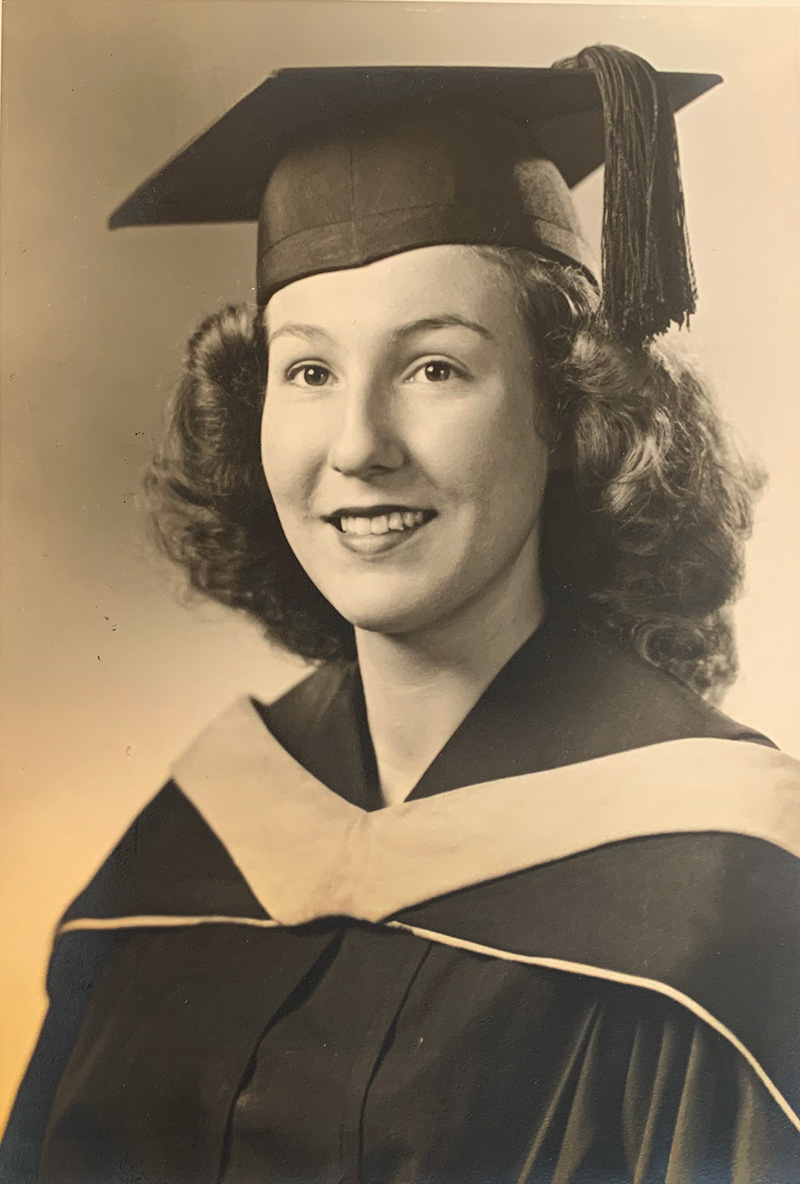 Black-and-white photo of Faye Demetriou in a graduation mortarboard and gown.