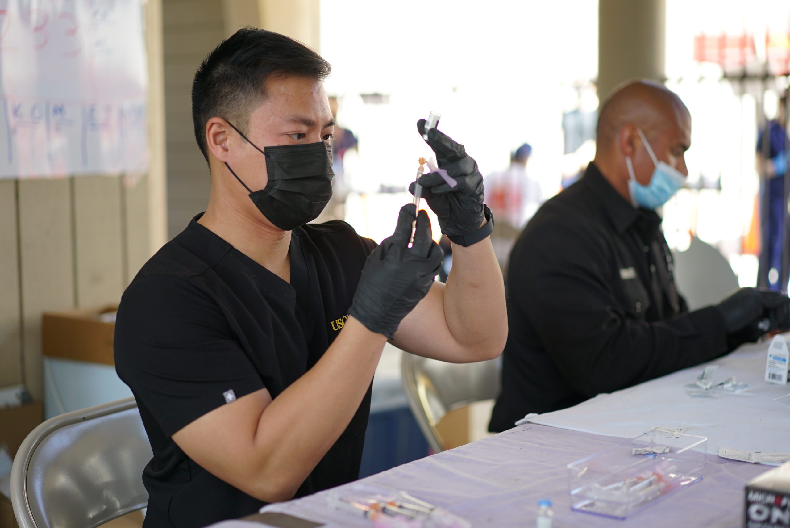 Richard Dang seated at a table in black medical scrubs, gloves and a mask filling a syringe from a vial of COVID-19 vaccine