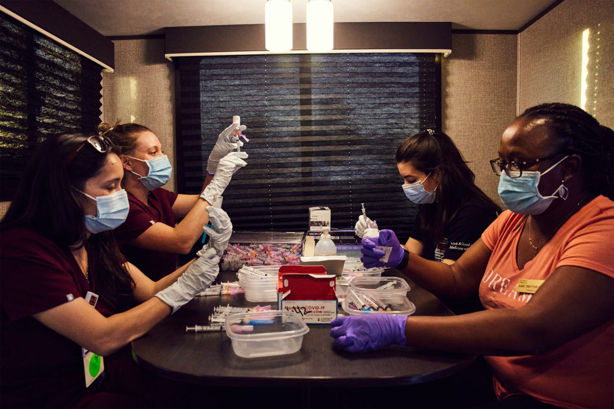 USC pharmacy professionals seated around a table wearing masks, gloves and medical scrubs and filling syringes with COVID-19 vaccines from vials