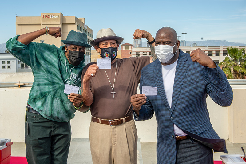 Arsenio Hall, Danny Trejo, and Magic Johnson hold up their COVID-19 vaccine cards and flex their biceps on a rooftop with with downtown Los Angeles in the background