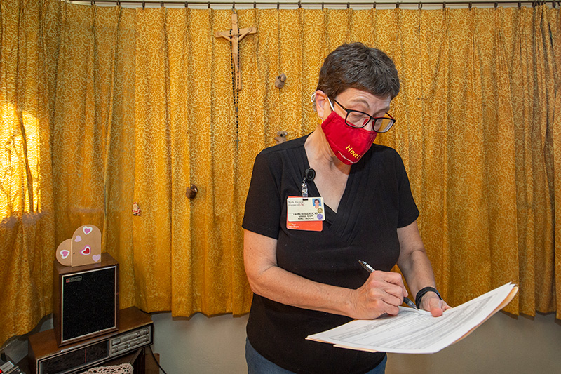 Laura Mosqueda in a black t-shirt and red USC facemask marking a medical form in a patient's home