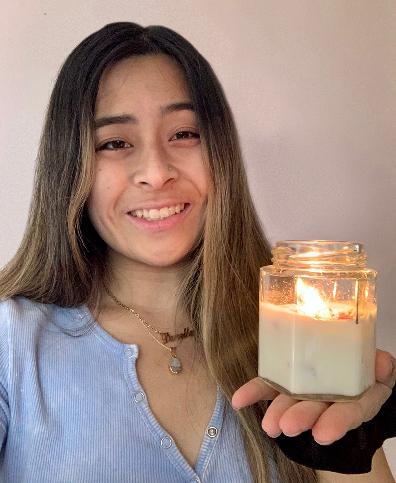 Danelle Go holding a lit candle in a glass jar
