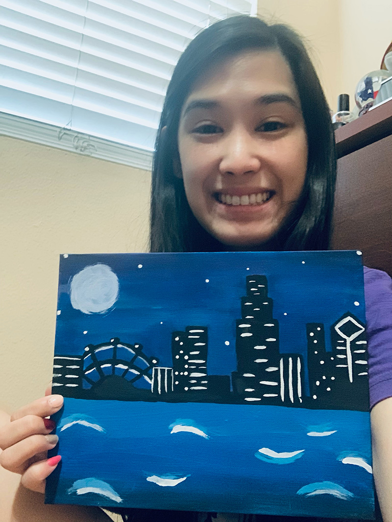 Whitney Tang displaying a blue painting of a skyline at night with water in the foreground