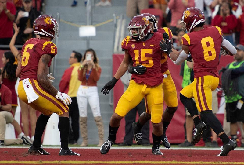 USC football players celebrate a touchdown in the end zone as Beverly Pham takes a photo on her cellphone in the background