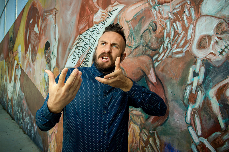 David A. Romero in a blue shirt with white dots gestures with upraised palms while standing against a wall painted with a mural