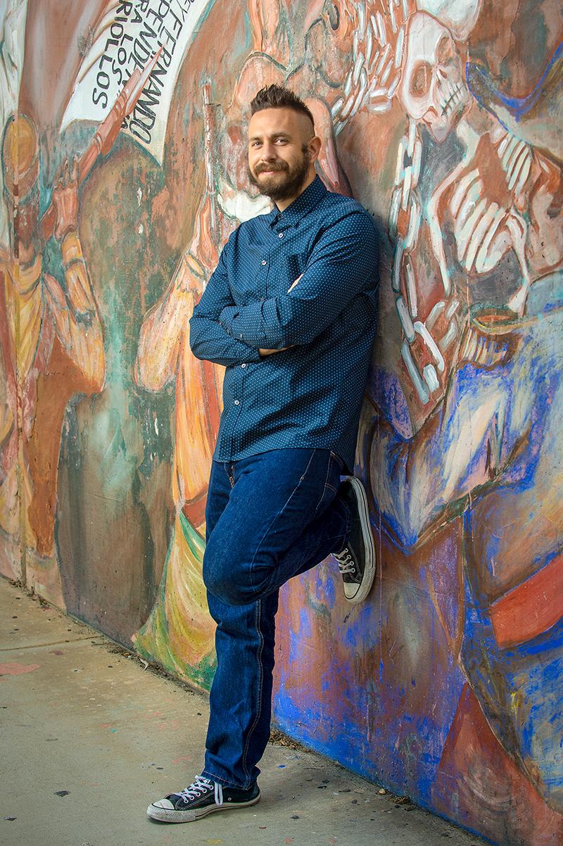 poet David Romero posed with mural