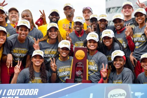 Women's track and field team with championship trophy