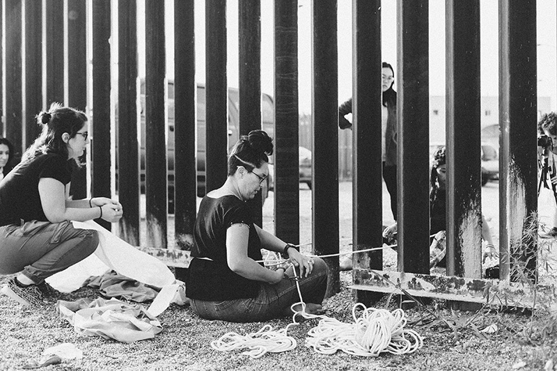 Artist Tanya Aguiñiga seated in front of the U.S.-Mexico border fence with string and other material on the ground around her