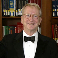 David C. Bohnett in a white button-down suit, black bowtie and black suit jacket with a bookcase in the background