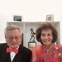 Lunny Ronnie Jung in a white button-down shirt, pink bowtie and black suit jacket and Dianne Kwock in a red dress and necklace with a bookshelf in the background