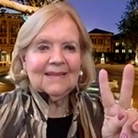 Patsy Dewey in a beige and brown patterned jacket and black shirt holding two fingers up in the USC victory sign