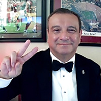 Richard Flores in a white button-down shirt, black bowtie and black suit jacket holding up two fingers in the USC victory sign