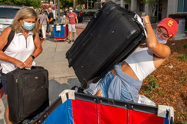 Callie Birtman and her mother, Amy, wrestle luggage