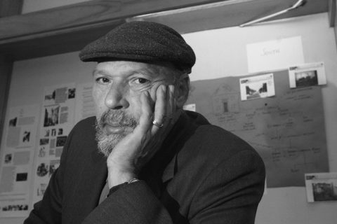 August Wilson in a dark flat cap and black suit jacket resting his chin on his hand