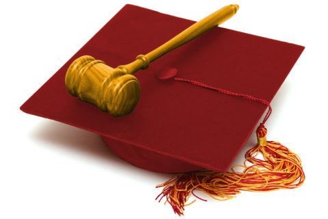 A wooden gavel on top of a cardinal mortarboard with a red and cardinal tassel