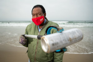 A USC alumnus in a green jacket and cardinal face mask holds an aluminum can in front of him with a trash grabber with the ocean in the background